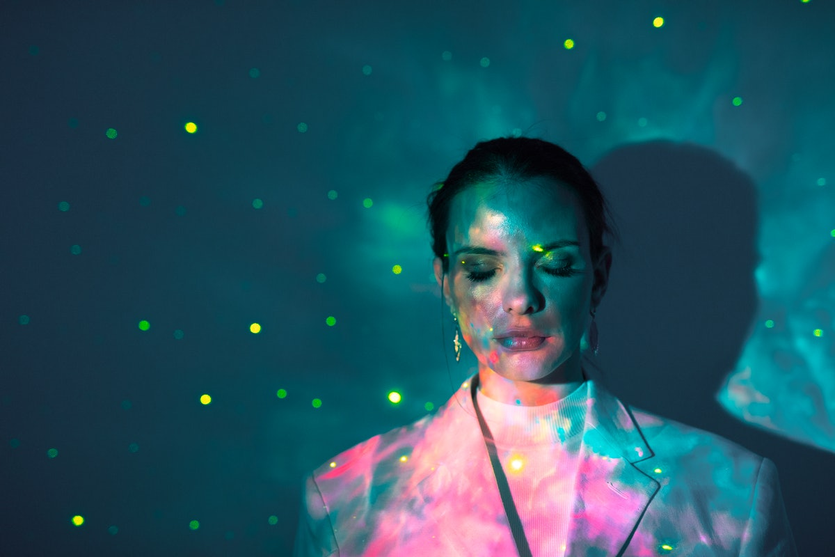 Young woman closing her eyes in glowing lights during the September 2021 new moon in Virgo, which af...