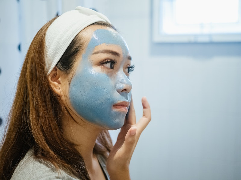 Asian woman in bathroom with facial mask, Home spa and skin care concept.