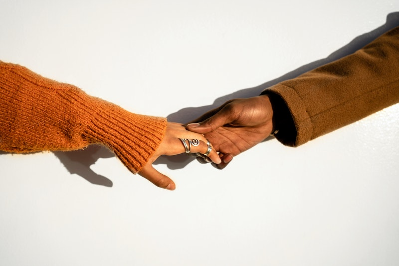 Crop woman in orange sweater and rings holding hand of black boyfriend in brown coat against wall in...
