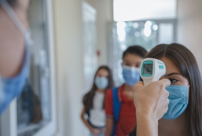 A female teacher using no-touch medical thermometer for check body temperature scanned measurement o...