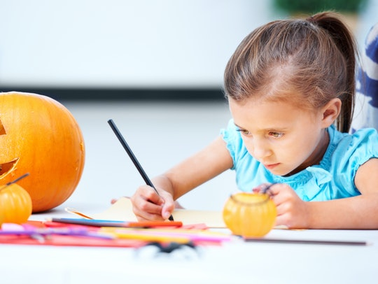 little girl coloring halloween picture with pumpkin