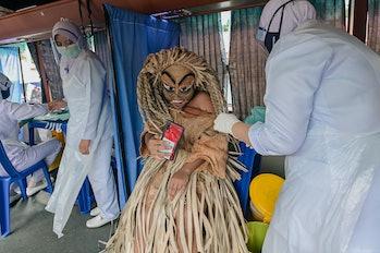An indigenous man of Mahmeri tribe wearing a costume of Puteri Gunung Ledang character takes a selfi...