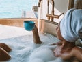Woman in hot tub relaxing and enjoying the tropical sea view