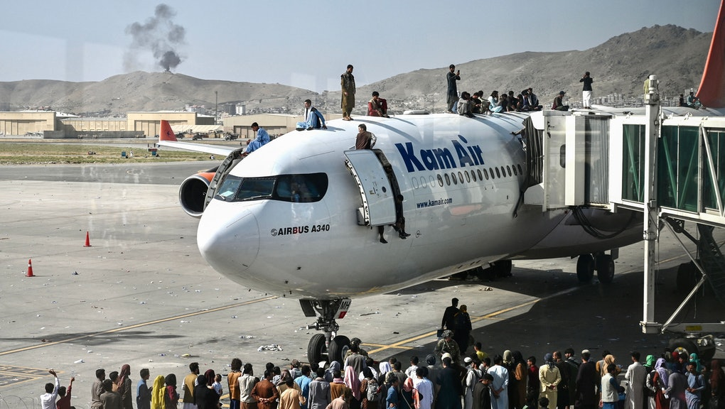 TOPSHOT - Afghan people climb atop a plane as they wait at the Kabul airport in Kabul on August 16, ...