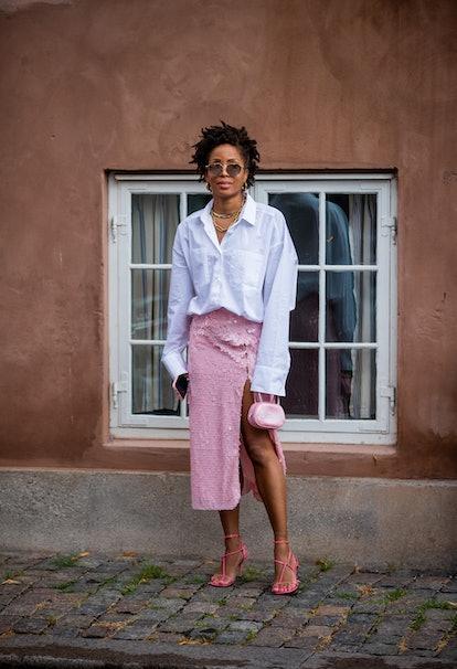 COPENHAGEN, DENMARK - AUGUST 10: A guest is seen wearing pink skirt, white button shirt outside Love...