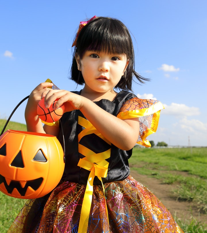 little girl dressed up in halloween costume standing outside