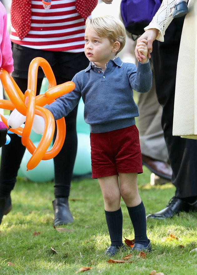 Prince George regally accepts a balloon animal.