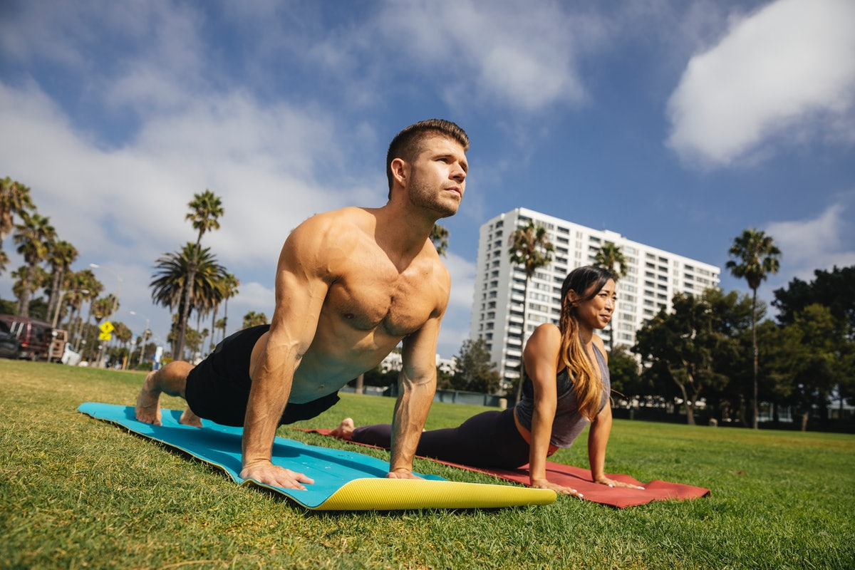 Young earth sign couple goes on an outdoor yoga date.