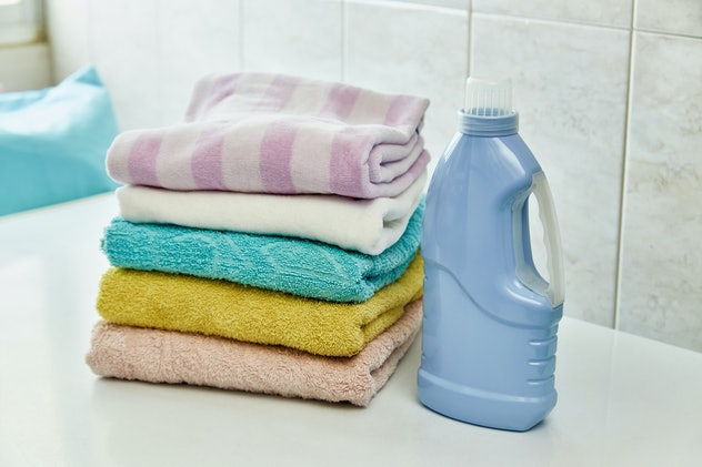 Stack of soft and colorful towels on table with detergent