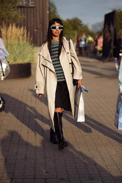 COPENHAGEN, DENMARK - AUGUST 12: Guest wearing black skirt, long boots and beige coat outside Rotate...