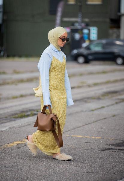 COPENHAGEN, DENMARK - AUGUST 11: A guest is seen wearing head scarf, dress, brown bag outside Samsøe...