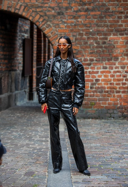 COPENHAGEN, DENMARK - AUGUST 10: A guest ist seen wearing black cropped jacket and pants latex outsi...