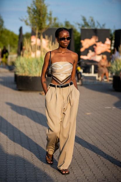 COPENHAGEN, DENMARK - AUGUST 12: A guest is seen wearing beige pants, cropped top outside Rotate on ...