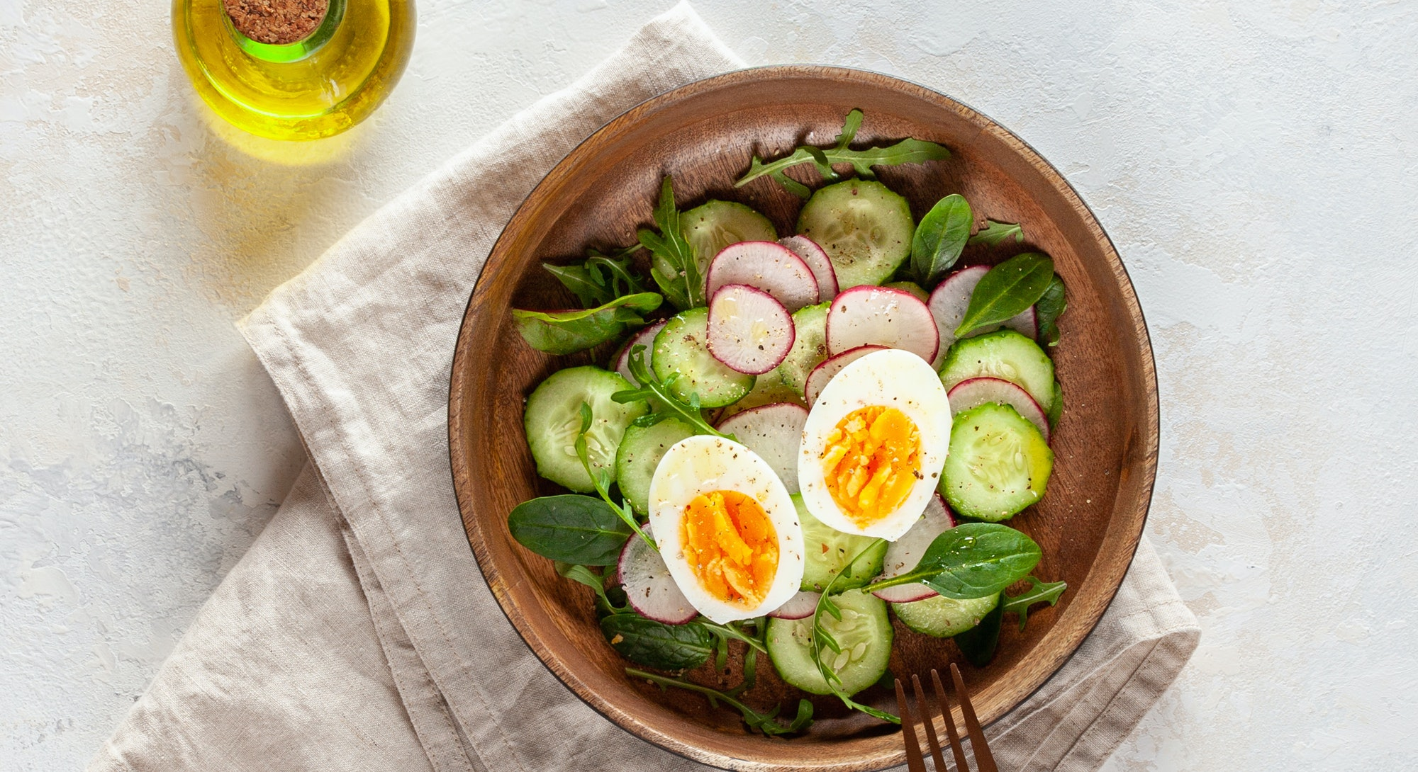 salad of radish, cucumber, arugula and boiled egg with olive oil in a wooden bowl