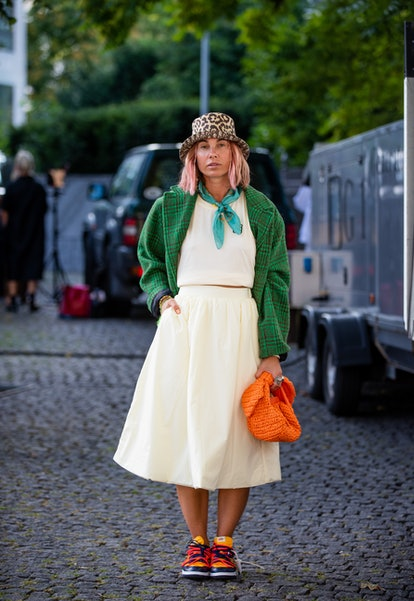 COPENHAGEN, DENMARK - AUGUST 11: Karin Teigl seen wearing hat, skirt, top, green jacket, orange bag ...
