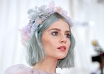 Lucy Boynton wears a flower crown and pastel hair and eye makeup with small rhinestone starbursts co...