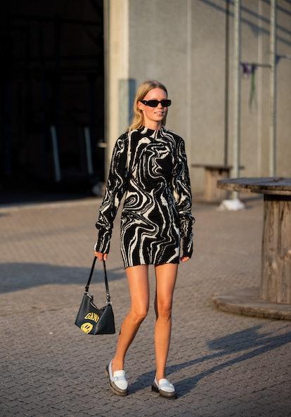 COPENHAGEN, DENMARK - AUGUST 12: A guest is seen wearing Prada sunglasses, Ganni bag, dress with zeb...