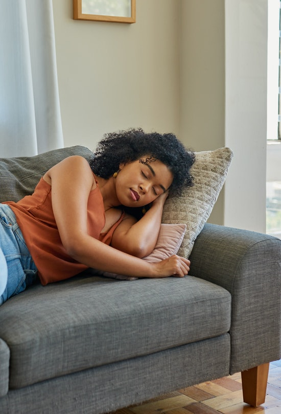 Shot of a young woman sleeping on a sofa at home