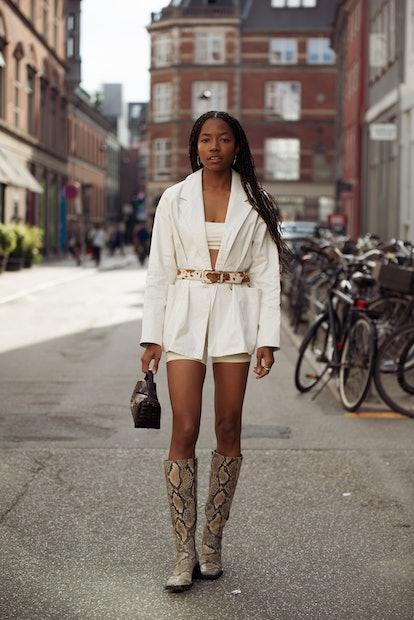 COPENHAGEN, DENMARK - AUGUST 11: Bria Jones wearing light short shorts, crop top, blazer with a belt...