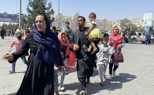 KABUL, AFGHANISTAN-AUGUST 16: An Afghan family rushes to the Hamid Karzai International Airport as t...