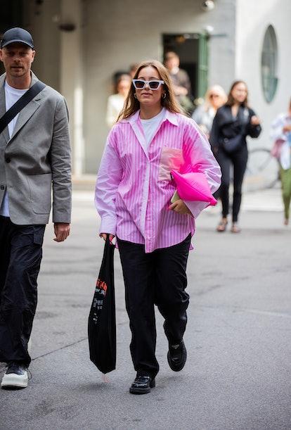 COPENHAGEN, DENMARK - AUGUST 10: A guest is seen wearing pink striped button shirt outside (di)visio...
