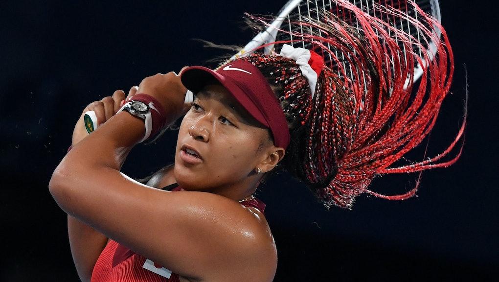 Japan's Naomi Osaka returns the ball to Czech Republic's Marketa Vondrousova during their Tokyo 2020...