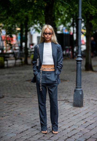 COPENHAGEN, DENMARK - AUGUST 10:  Vanessa Hong is seen wearing cropped top, belt, grey striped suit ...