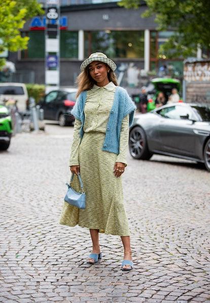 COPENHAGEN, DENMARK - AUGUST 10: A guest is seen wearing green skirt and button shirt, hat outside 7...