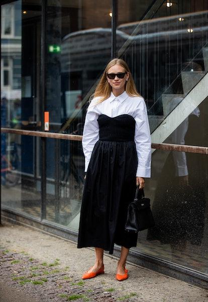 COPENHAGEN, DENMARK - AUGUST 10: Tine Andrea is seen wearing black dress, white button shirt outside...