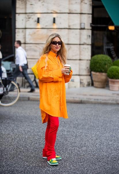 COPENHAGEN, DENMARK - AUGUST 10: Emili Sindlev seen wearing orange jacket, red pants outside The Gar...