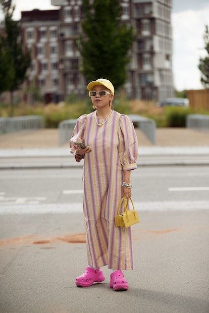 COPENHAGEN, DENMARK - AUGUST 11: Guest wearing long striped dress, yellow hat and pink shoes  outsid...