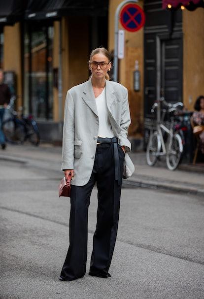 COPENHAGEN, DENMARK - AUGUST 09: A guest is seen wearing grey blazer, black pants, Acne bag, sunglas...