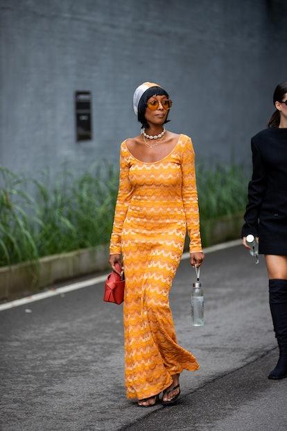 COPENHAGEN, DENMARK - AUGUST 10: A guest is seen wearing orange dress, head scarf outside (di)vision...