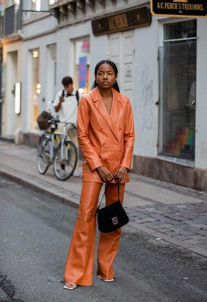 COPENHAGEN, DENMARK - AUGUST 10: A guest is seen wearing orange brown jacket and pants outside Soere...