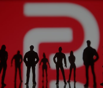 UKRAINE - 2021/01/10: In this photo illustration the Parler logo seen in front of the silhouettes of...