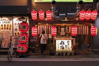 OSAKA, JAPAN - AUGUST 02: A customer wearing a protective face mask leaves after dining at a restaur...