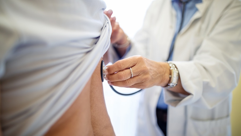 Cropped of female doctor examining patient. Medical professional checking woman's back with stethosc...