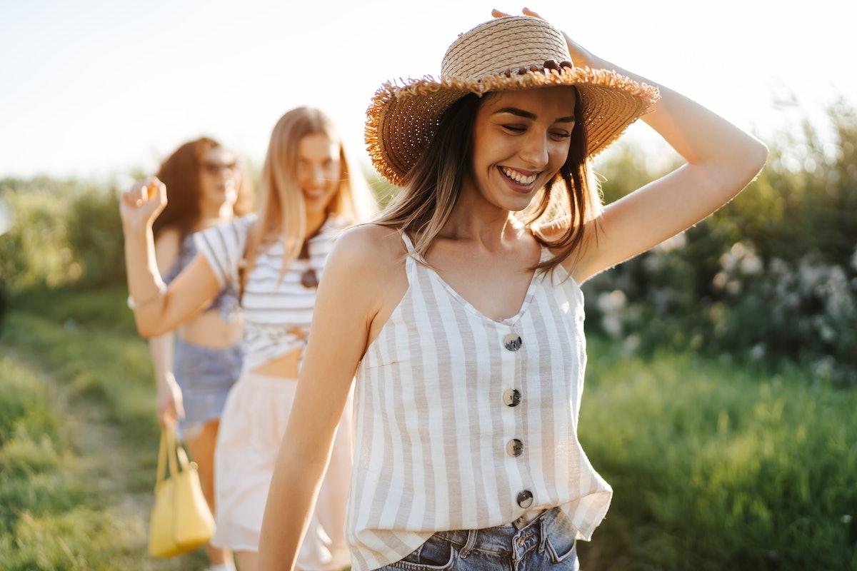 Three happy young female friends enjoying summer walk in nature