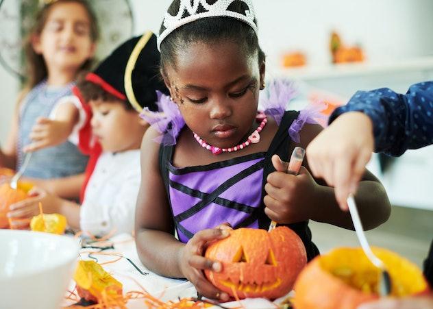 little girl in a princess costume making a jack o lantern