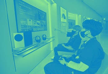 Staff members play on Microsoft's Xbox Series X gaming console at a flagship store of SK Telecom in ...