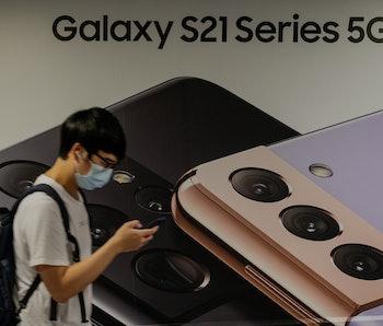 HONG KONG, CHINA - 2021/05/18: A man uses a smartphone as he walks past the South Korean multination...