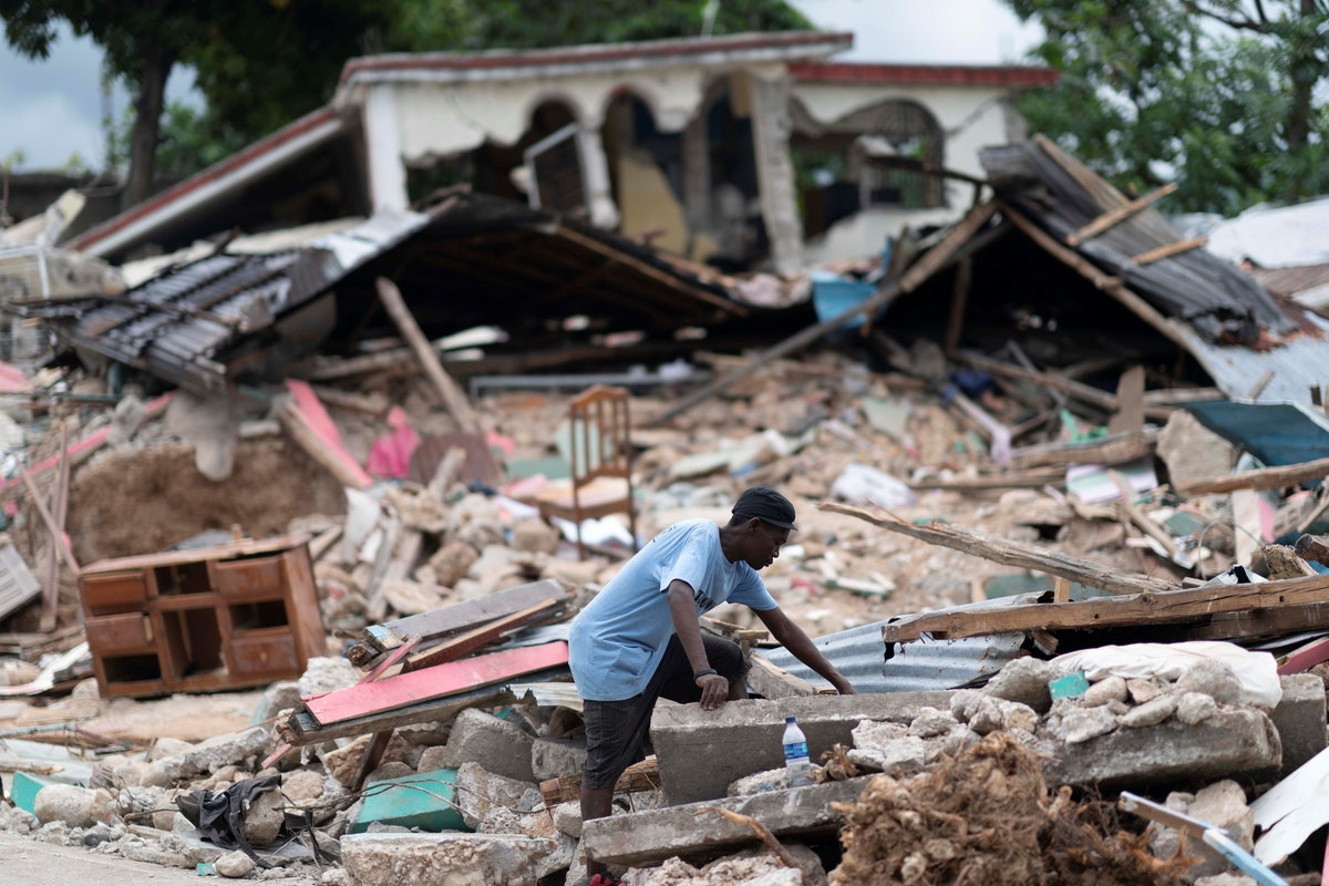 A man searches in the debris of a collapsed house after an earthquake, in Les Cayes, Haiti, on Aug. ...