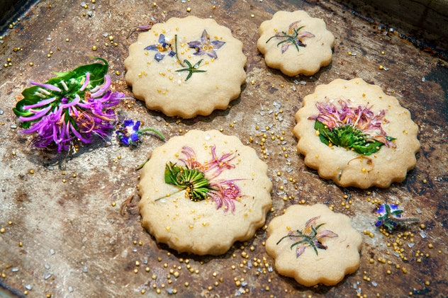 Image of shortbread cookies with edible flowers and gold sugar on top.