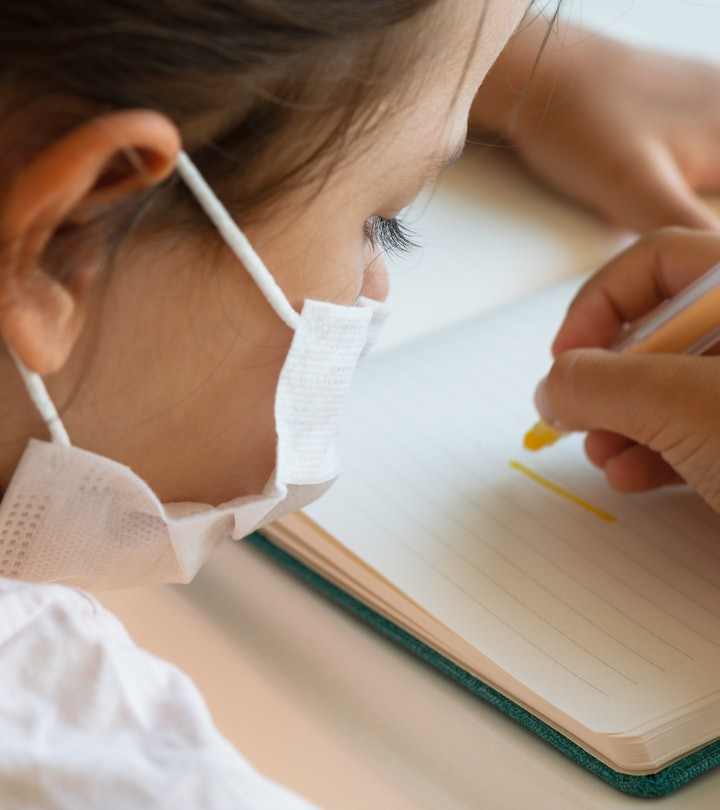 Over the shoulder  view of child with face mask is writing with yellow pen.