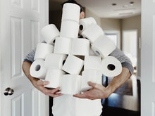 Close-up of unrecognizable man carrying an abundance of toilet paper
