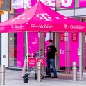NEW YORK, NEW YORK - AUGUST 18: A clerk at the T-Mobile store in Times Square provides curb side ser...