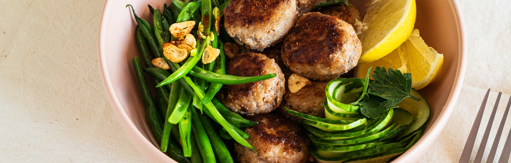 Rustic table with meal. Pork meatballs with sauteed green beans,  cucumber salad,  high angle view