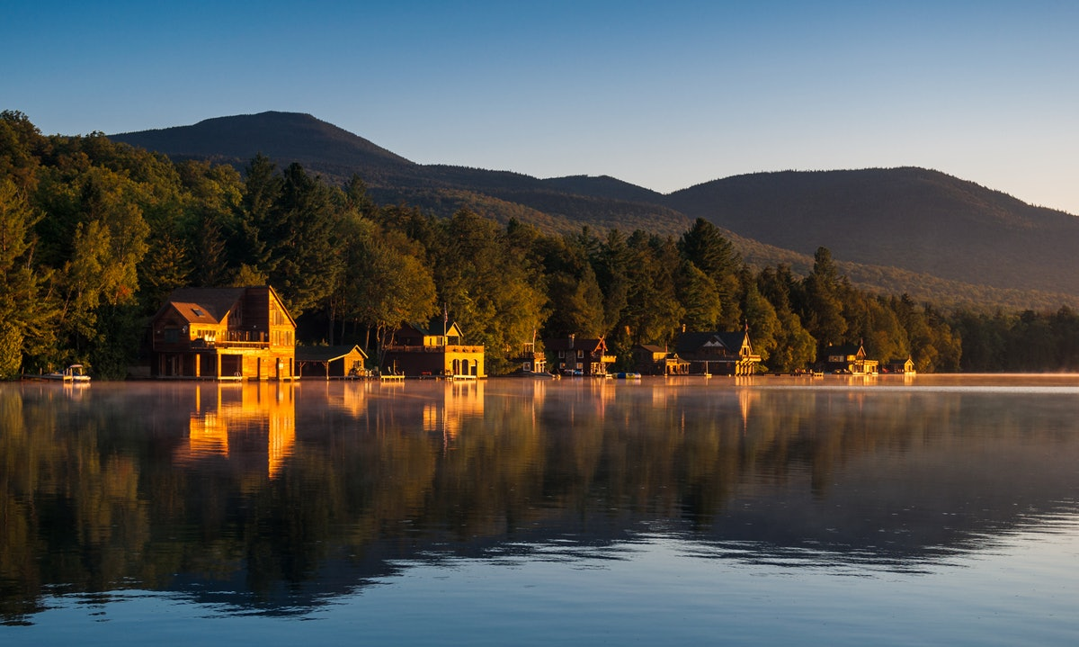 Wooden cabins around mountain town Lake Placid, NY, USA in early morning