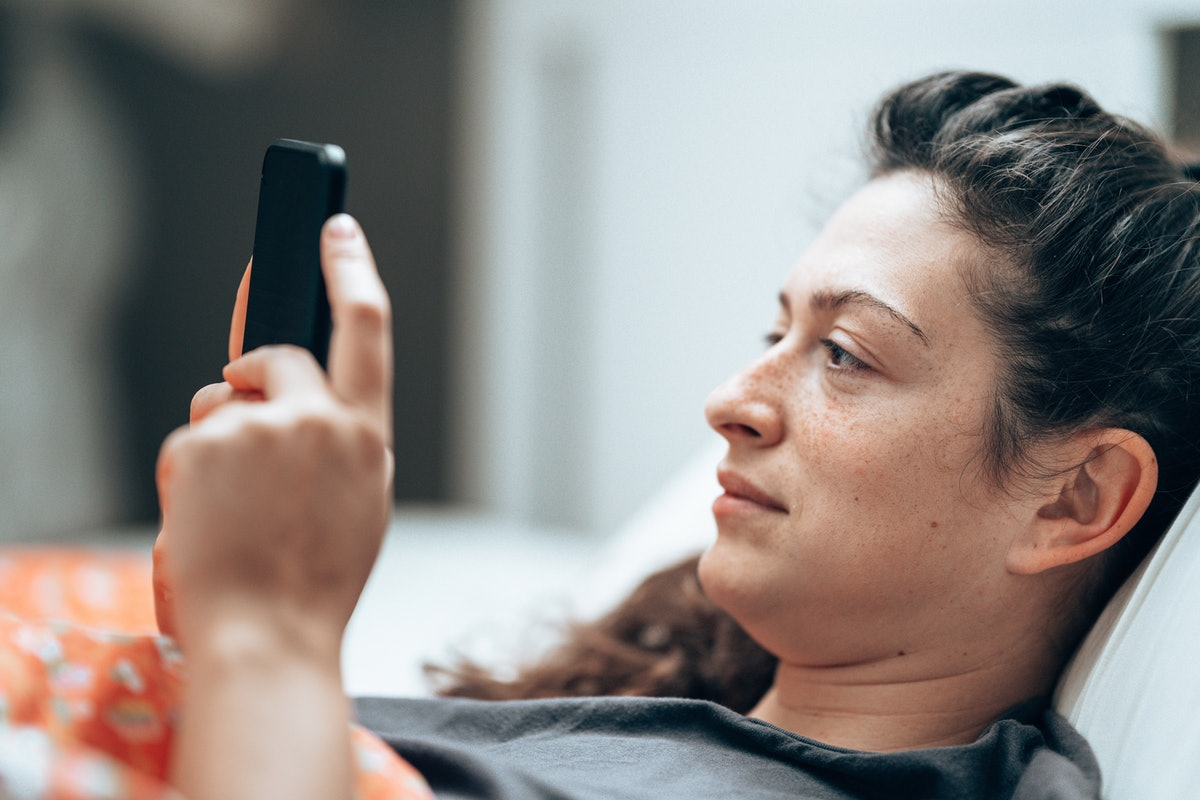 woman text messaging in the bed