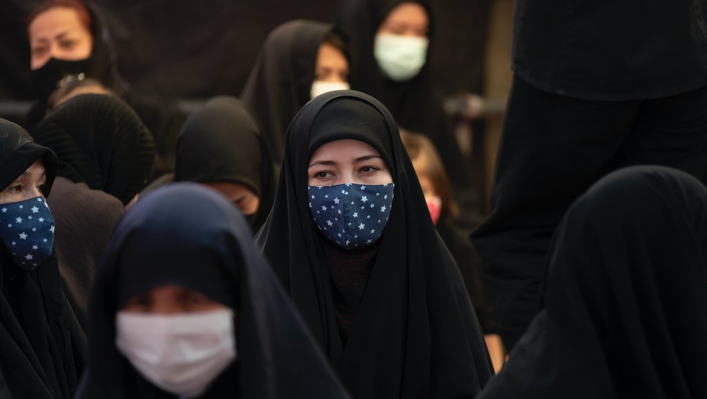 An Afghan refugee woman wearing a protective face mask looks on while attending a hussainiyah during...